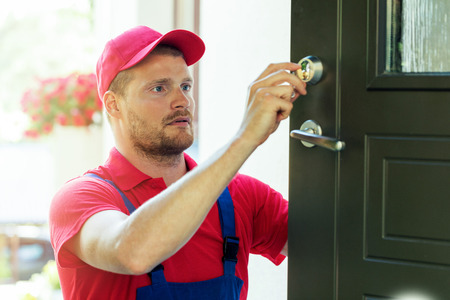 handyman fixing house door lock Banco de Imagens