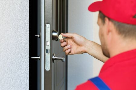 door lock service - locksmith working in red uniform photo