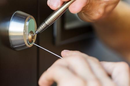 closeup of locksmith hands using pick tools to open locked door