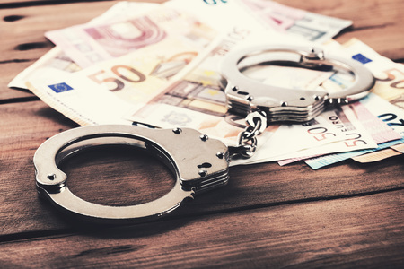 financial crime concept - money and handcuffs on the table