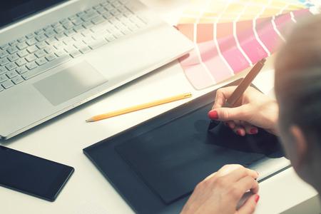 freelance graphic designer using digital drawing tablet photo