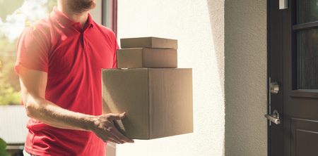 home delivery service - deliveryman with boxes standing by the house doors photo