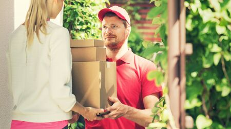 woman accepting a home delivery of boxes from deliveryman. copy space photo