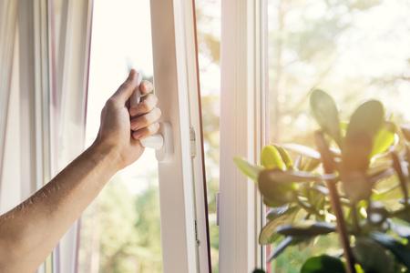 Hand offenes weißes Plastikpvcfenster zu Hause Standard-Bild - 83973586