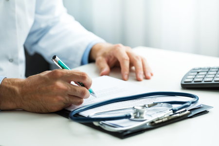 doctor writing prescription at desk in clinics office Reklamní fotografie