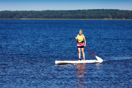 sup - woman on stand up paddle board in the lake