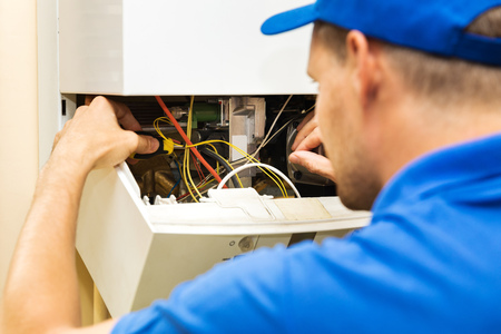 maintenance service engineer working with home gas heating boiler