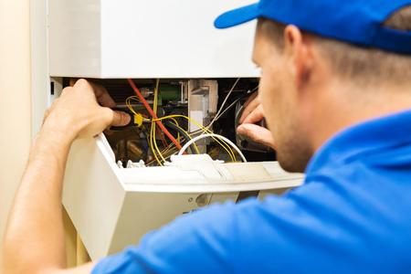 inżynier serwisu technicznego pracujący z domowym kotłem grzewczym