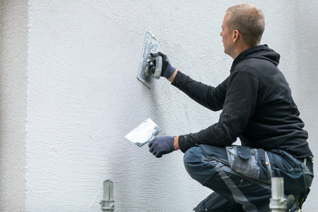 construction worker putting decorative plaster on house exterior Stock fotó - 87338998