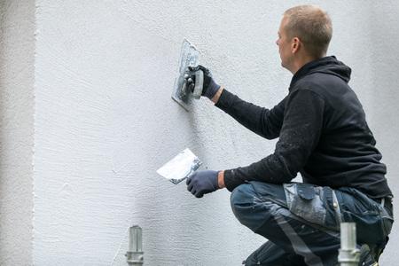 Operaio edile mettendo intonaco decorativo sulla casa all & # 39 ; aperto