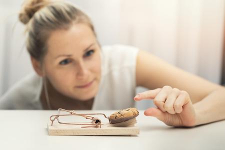 mujer hambrienta tratando de robar galletas de la trampa del ratón. concepto de plan de dieta de pérdida de peso