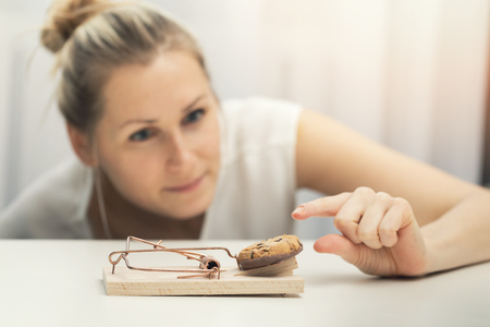 hungry woman trying to steal cookie from mouse trap. weight loss diet plan concept