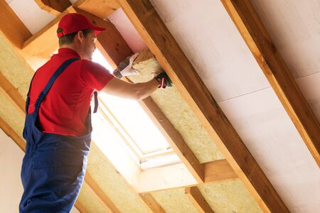 house attic insulation - construction worker installing rock wool in mansard wall