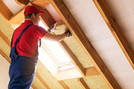 ocieplenie poddasza domu - robotnik budowlany instalujący wełnę mineralną w ścianie mansardowej