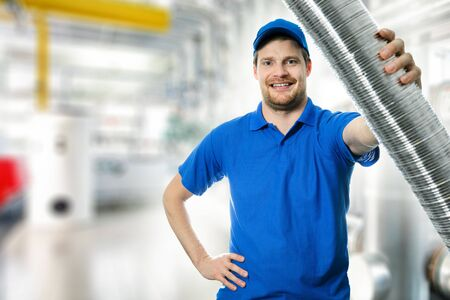 hvac technician with flexible aluminum ducting tube in hand