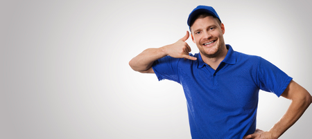 worker in blue uniform making phone call gesture