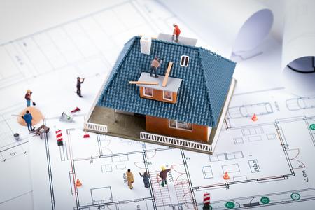 Hausbauprojektkonzept. Gebäudemodell und Arbeiter auf Blaupause Standard-Bild - 92569768
