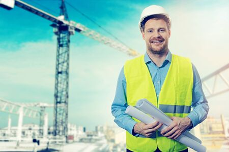 construction project engineer with blueprints at building site Stock Photo