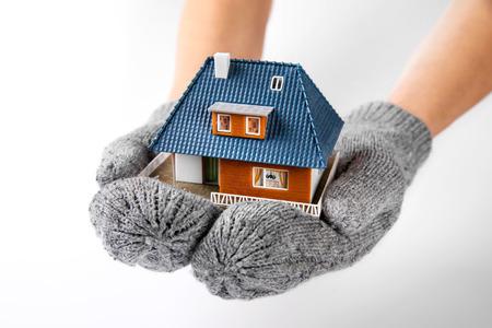 Huis verzekering en isolatie concept. handen met handschoenen miniatuur huis model te houden Stockfoto - 95681408