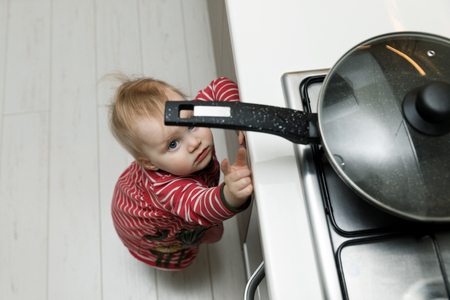child safety at home concept - toddler reaching for pan on the stove in kitchen