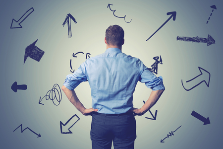 confused businessman with direction arrows. choosing the right way decision concept