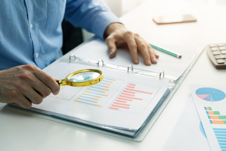 internal audit concept - man with magnifying glass inspecting business documents Foto de archivo