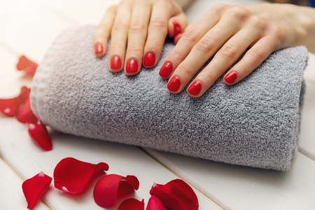 woman fingernails with red nail polish on towel roll perfect manicure