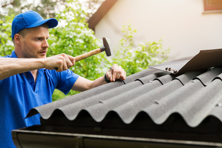 roofer installing bitumen roof sheets Archivio Fotografico