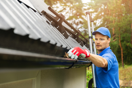 A worker cleaning house gutter from leaves and dirt