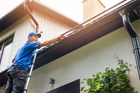 A man on ladder cleaning house gutter from leaves and dirt