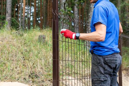 A worker installing welded metal mesh fence