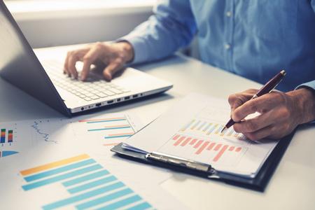 zakenman analyseren van bedrijfsjaarverslag met het gebruik van laptop op kantoor