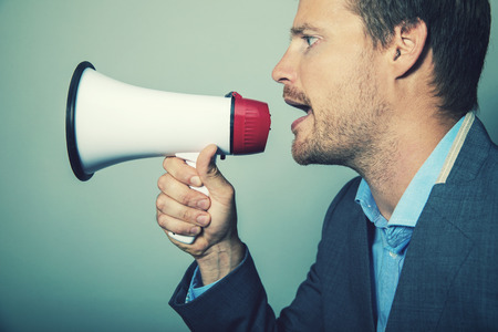 business leadership - businessman giving instructions with megaphone