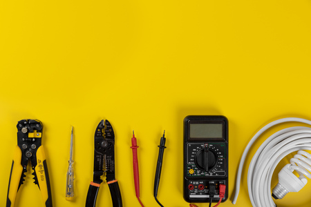 electrical installation tools on yellow background with copy space