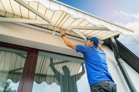 lavoratore installa una tenda da sole sul muro della casa sopra la finestra della terrazza Archivio Fotografico