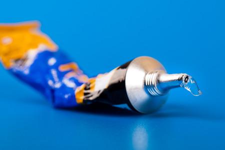 tube de super colle sur fond bleu