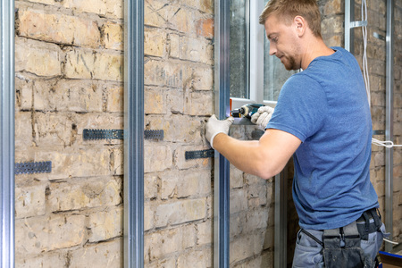 man installing metal profile frame on the old brick wall for plasterboard sheets Standard-Bild