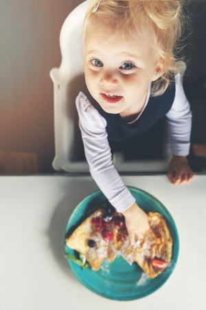 2 years old child eating pancakes. top view