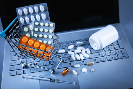 online pharmacy - shopping cart with pills on computer keyboard Stock Photo