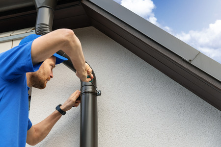 worker installing house roof gutter 免版税图像 - 115839934