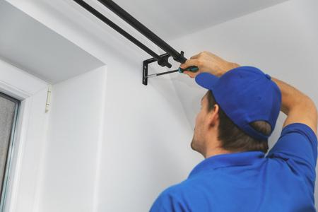 handyman services - worker installing window curtain rod on the wall Stockfoto