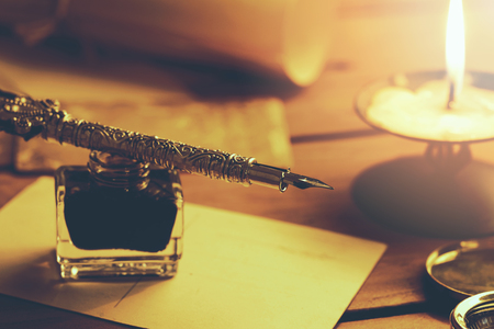 old quill pen and inkwell on brown wooden table with candle