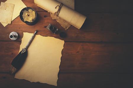 Federkiel und altes Pergamentpapier auf braunem Holztisch. Ansicht von oben