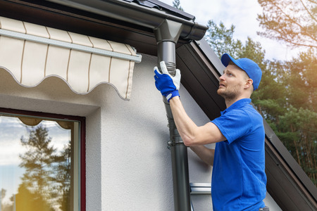 worker installing house roof rain gutter system