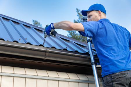 metalen dakbedekking - dakdekker die op het dak van het huis werkt