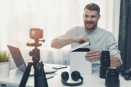 social media technology influencer recording unboxing video at home Stockfoto