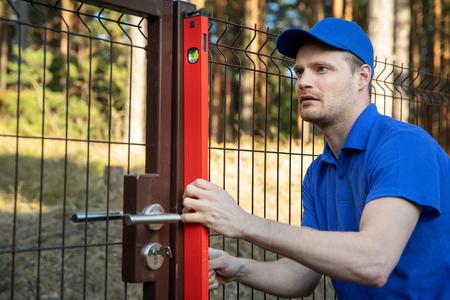 construction de clôture - travailleur vérifier le niveau de poteau métallique