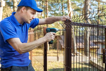 clôture de territoire de propriété - l'homme vis le panneau de clôture en métal Banque d'images