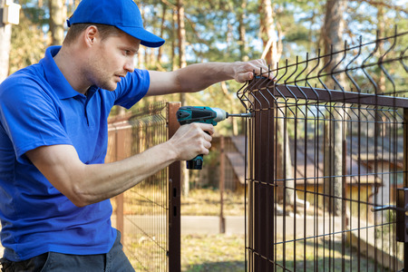 property territory fencing - man screws metal fence panel