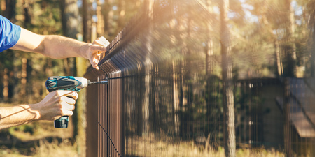 fencing - worker installing metal wire mesh fence panel Archivio Fotografico - 122292480
